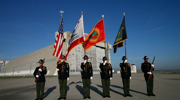 6 Honor Guard member standing at attention holding flags