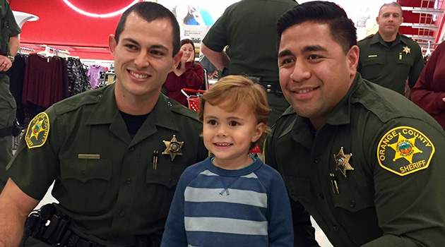 Two officers take a photo with a child